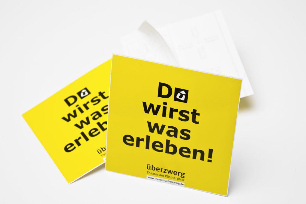 """Grafikdesign Überzwerg Theater Saarbrücken: Aufkleber """"Du wirst was erleben"""""""
